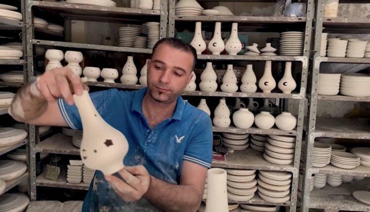 خزّاف الفلسطيني محمد النتشة يحمل قطعة خزفية صنعها من الفخار
