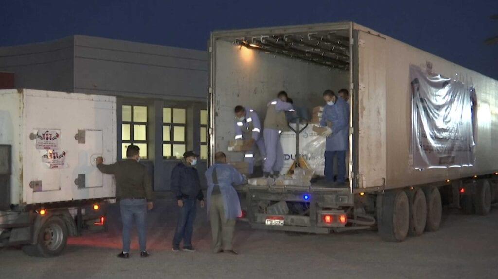 """عمال يفرغون شاحنة مساعدات في قطاع غزة، وصلت عبر معبر رفح البري مع مصر، تحتوي على 40 الف جرعة من لقاح """"سبوتنيك في"""" تبرعت بها الامارات العربية"""