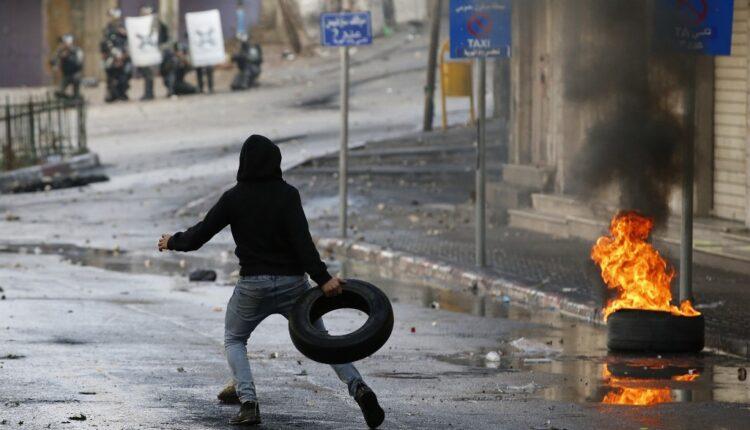 متظاهر فلسطيني يلقي بإطار خلال مواجهات مع قوات الأمن الإسرائيلية في مدينة الخليل جنوب الضفة الغربية ، 9 ديسمبر ، 2019 (الصورة: AFP)