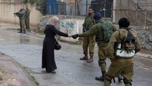 جنود إسرائيليون يفحصون هوية امرأة فلسطينية في حي تل الرميدة بالخليل ، الضفة الغربية المحتلة. (الصورة: AFP)
