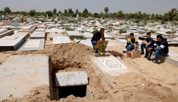 فلسطينيون ينتظرون دفن جثة قريبهم الذي توفي بعد إصابته بفيروس كورونا (كوفيد -19) في مقبرة شرقي مدينة غزة يوم 20 أبريل نيسان 2021. (الصورة: رويترز)