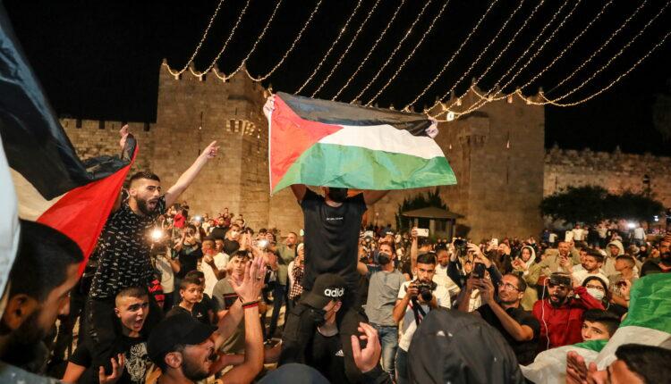 فلسطينيون يلوحون بالأعلام ويحتفلون خارج باب العامود بعد إزالة الحواجز التي أقامتها الشرطة الإسرائيلية ، مما يسمح لهم بالوصول إلى الميدان الرئيسي الذي كان محور الاشتباكات حول البلدة القديمة في القدس في 25 أبريل 2021. (الصورة: رويترز)