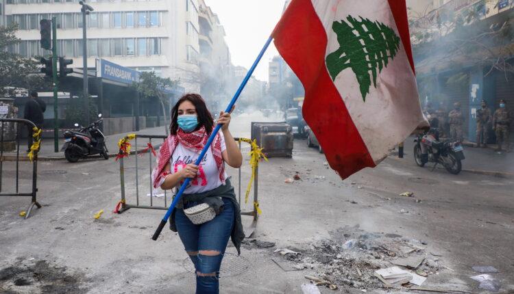 متظاهرة تحمل علم لبنان في بيروت (الصورة: أرشيف/رويترز)