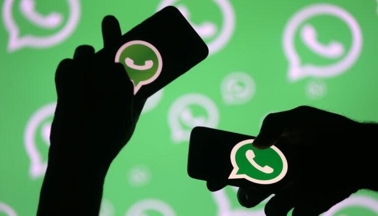 رجال يقفون مع هواتفهم الذكية أمام شعار Whatsapp المعروض في هذا الرسم التوضيحي ، 14 سبتمبر ، 2017. (الصورة: رويترز)