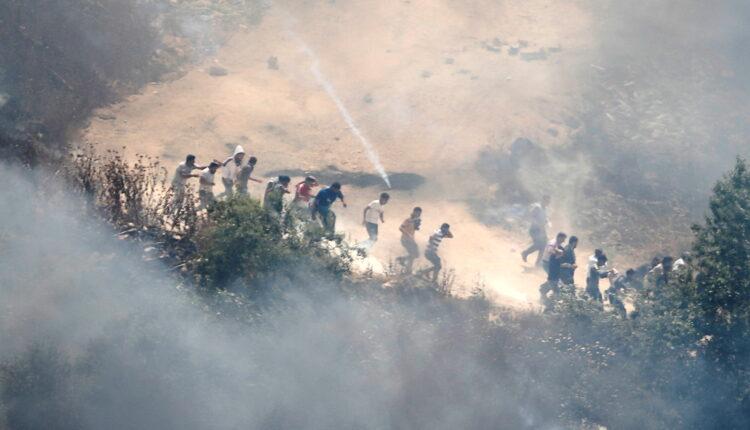 متظاهرون فلسطينيون يحاولون الهرب من الغاز المسيل للدموع الذي أطلقه جنود إسرائيليون في الضفة الغربية يوم الجمعة. (الصورة: رويترز)