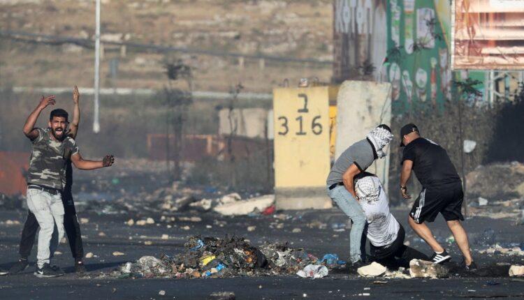 متظاهرون يساعدون متظاهرا مصابا خلال مظاهرة بالقرب من مستوطنة بيت إيل اليهودية بالقرب من رام الله ، في الضفة الغربية المحتلة 18 مايو ، 2021. (الصورة: رويترز)