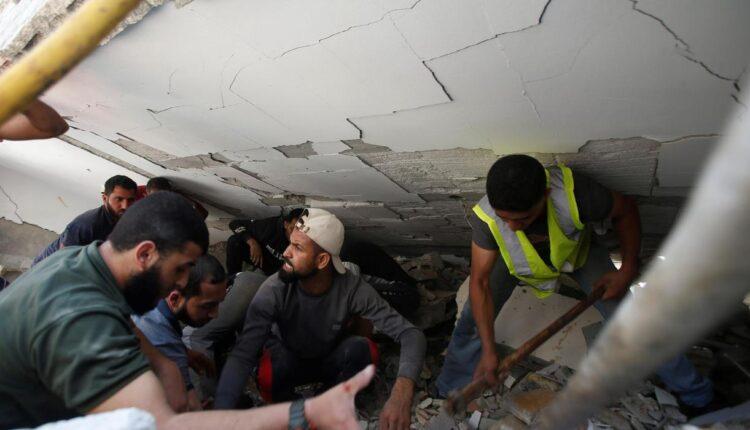 عمال الإنقاذ يبحثون عن ضحايا وسط الأنقاض في موقع الضربات الجوية الإسرائيلية في مدينة غزة صباح الأحد 17 مايو 2021. (الصورة: رويترز)