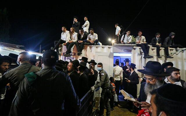 مسؤولون أمنيون وعمال إنقاذ إسرائيليون يحملون جثة ضحية ماتت خلال احتفالات  في جبل ميرون، 30 أبريل 2021 (الصورة: AP)
